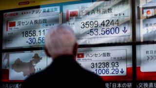 Чоловік у Токіо спостерігає за падінням фондових індексів