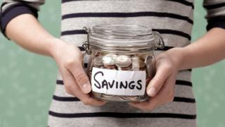 Woman holding savings jar