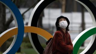 Woman wearing a face mask walks past the Olympic rings in Tokyo
