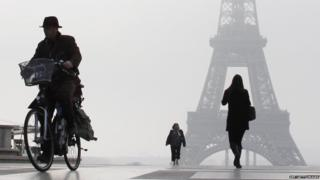 A man rides a bicycle on the Esplanade du Trocadero in front of the Eiffel tower, on March 11, 2014