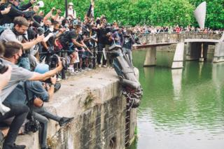 in_pictures A large crowd of people watch as a statue is thrown into a harbour