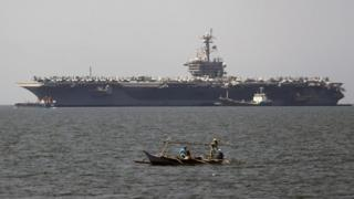 "Filipino fishermen in a boat manoeuvre next to the US aircraft carrier ""USS Carl Vinson"" at the Manila Bay, Philippines, 17 February 2018."