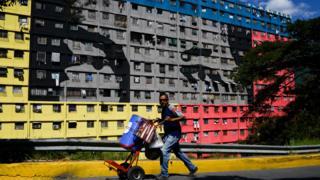 Venezolano en el 23 de enero con la imagen de Chávez de fondo