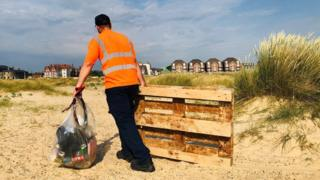 environment A litter picker on Great Yarmouth beach