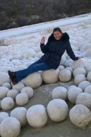 A picture showing a smiling woman lying across the snowballs in the Yamal Peninsula