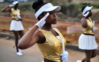 South African majorettes salute as they parade near the house of Winnie Mandela Soweto, Johannesburg, on April 8, 2018.