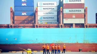 Chinese workers look as a cargo ship is loaded at a port in Qingdao, eastern China's Shandong province on July 13, 2017.