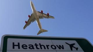 A plane flying over a Heathrow sign