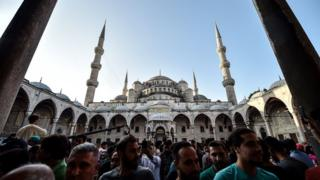 Muslim worshippers leave the Blue Mosque after the Eid al-Fitr prayers in Istanbul, 25 June