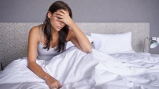 Mujer en la cama agarrándose la cabeza