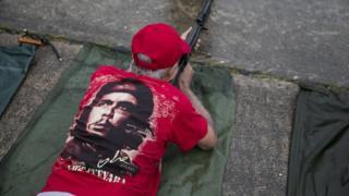 Мужчина в майке с портретом Че Гевары и ружьем в руках