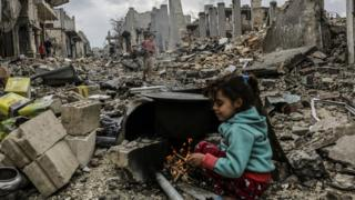 A Syrian girl hides in the ruins of the bombed out city of Kobabe