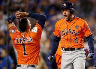 George Springer celebra con Carlos Correa una carrera de los Astros.