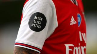 Arsenal player with Black Luves Matter logo on their shirt sleeve.