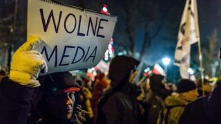 A protester holds a sign reading 'Free media' as people gather for an anti-government demonstration by opposition supporters outside the Polish parliament on 16 December 2016.