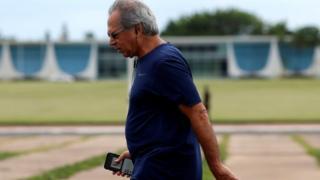 Paulo Guedes com roupa esportiva caminhando em frente ao Palácio da Alvorada