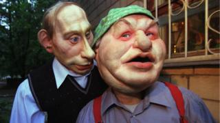 Puppet of Russian President Vladimir Putin, left, whispers a word to Moscow's mayor Yuri Luzhkov, June 29, 2000
