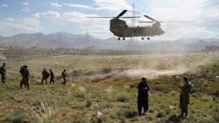 US military Chinook helicopter lands on a field