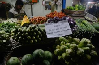 An Indian vendor displays a sign relating to new currency regulations as he waits for customers, following the decision to withdraw the current 500 and 1000 INR notes, in Siliguri on November 13, 2016.