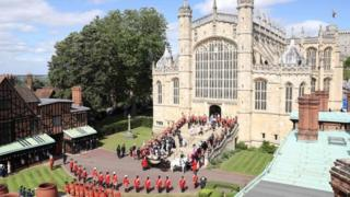 The Knights of the Garter, guards, military and members of the Royal Family surround the west steps at St George's Chapel