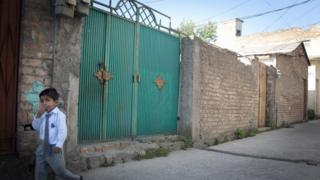 A school boy walks past the gates of Shakil Rafiq's home