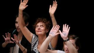 Susan Sarandon at demonstration, holding hands above her head