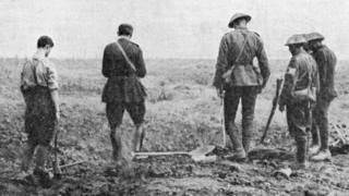 Army chaplain conducting burial service in the field, c.1916.