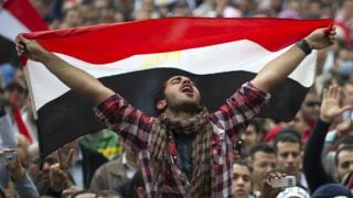 Hombre con una bandera de Egipto en una protesta en 2011