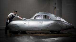 A man polishes a Porsche at Sotheby's