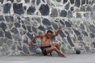 "A man plays a pre-Columbian ballgame called ""Ulama"" -in Nahuatl indigenous language- which rule is to hit a ""Ulamaloni"" (solid rubber ball) with the hip or shoulder, during a match at the FARO Poniente cultural centre in Mexico City on August 21, 2019"