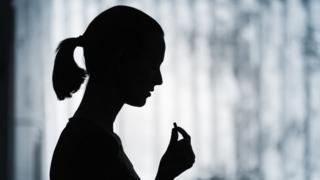 Perfil de una mujer tomando una pastilla
