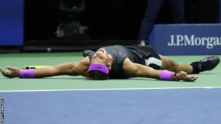 Rafael Nadal lies on the ground in celebration