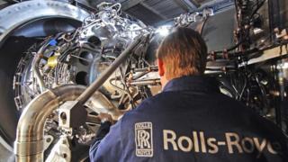 A Rolls-Royce employee working on an engine