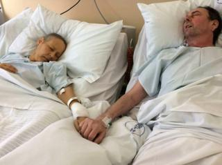 Julie and Mike Bennet in hospital holding hands