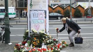 Женщина возлагает цветы к памятнику жертвам инцидента