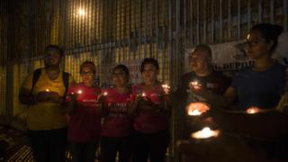 """Activists pray at the wall between Mexico and US during a protest against the possibility of deportation of """"Dreamers"""" in Playas de Tijuana, Baja California, Mexico, 4 September"""