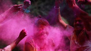 People throw paint during the festival of Holi