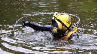 A police diver enters the lake as part of the search