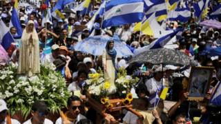 Demonstrators hold national flags during a march in support of the Catholic Church in Managua, Nicaragua July 28, 2018.