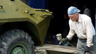 Man spray-painting part of an armoured personnel carrier