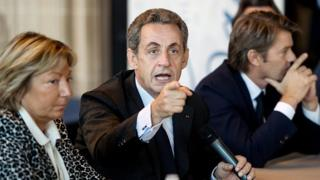 Former French president and hopeful candidate for the right-wing Les Republicains (LR) party in 2017 presidential election Nicolas Sarkozy (C) flanked by Calais Mayor Natacha Bouchart (L) and LR party member Francois Baroin, gestures as he speaks in Calais' town hall, northern France, on 21 September 2016