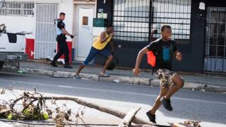 A soldier of the French Gendarmerie chases alleged looters as they run past the devastation from Hurricane Irma on the island of St Martin (08 September 2017)