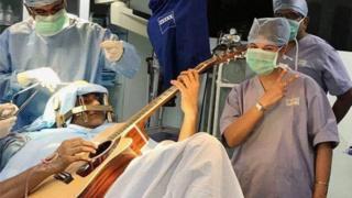 هندي يعزف الغيتار اثناء خضوعه لجراحة في الدماغ
