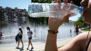 Mujer bebiendo agua durante una ola de calor