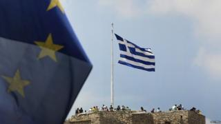 A European Union flag flutters as tourists gather around a Greek flag atop the Acropolis hill in Athens
