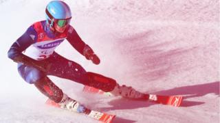 An action shot of a slalom run competitor travelling fast with a red hue over the photo