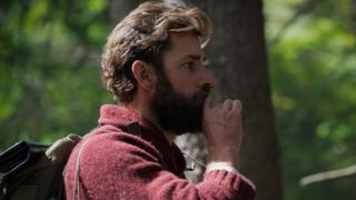 John Krasinski hushing with fingertip in still from the film