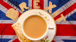 Brexit spelled in biscuits above a cup of tea, sat on a Union flag painted board