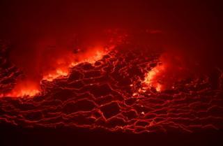 Molten lava cracks and bubbles red.