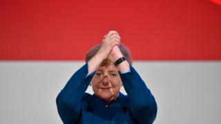 """German Chancellor and leader of the Christian Democratic Union (CDU) Angela Merkel acknowledges the applause after delivering her speech at a party congress of Germany""""s conservative Christian Democratic Union (CDU) party on December 7, 2018 at a fair hall in Hamburg, northern Germany. - German Chancellor Angela Merkel will hand off leadership of her party after nearly two decades at the helm, with the race wide open between a loyal deputy and a longtime rival. (Photo by John MACDOUGALL / AFP)JOHN MACDOUGALL/AFP/Getty Images"""